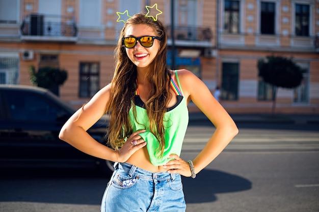 Mujer joven en la calle con camiseta verde, jeans, gafas de sol y estrellas de neón en la cabeza.