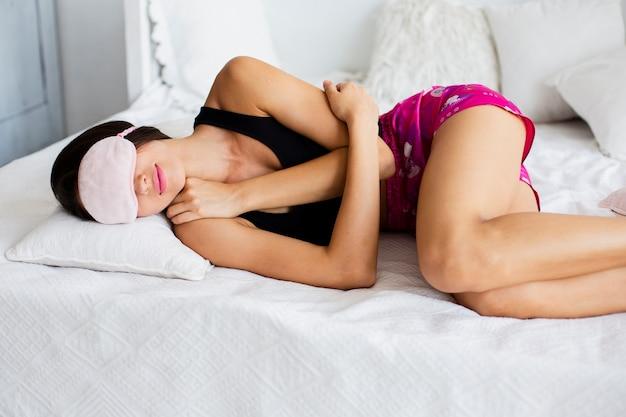 Mujer joven en la cama con antifaz para dormir
