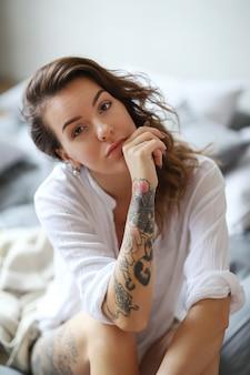 Mujer joven en la cama por la mañana