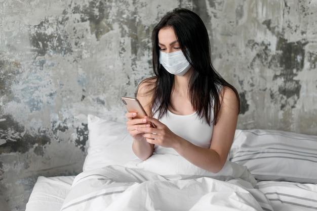 Mujer joven en la cama con mascarilla