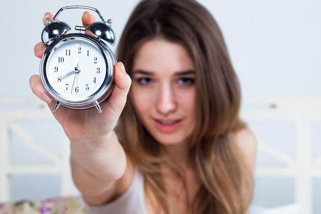 Mujer joven en la cama con reloj despertador