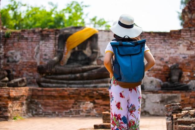 Una mujer joven camina en el viejo templo en phra nakhon si ayutthaya, tailandia en un día relajante.