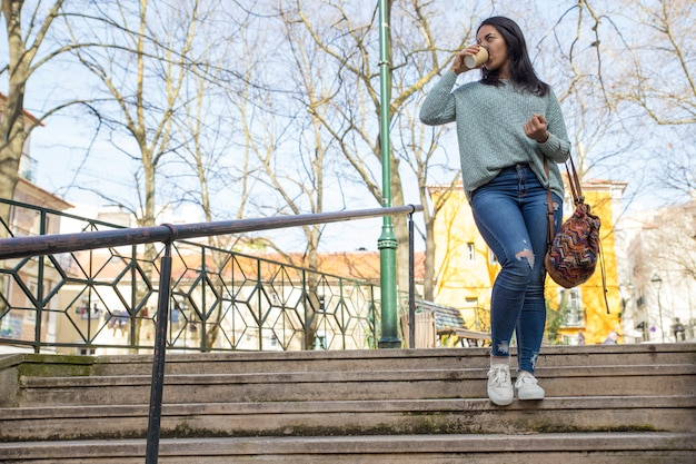 Mujer joven caminando por las escaleras de la ciudad y tomando café