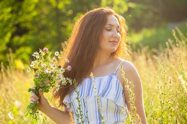 Mujer joven caminando entre flores silvestres en un día soleado de verano concepto de la alegría de comunicarse con
