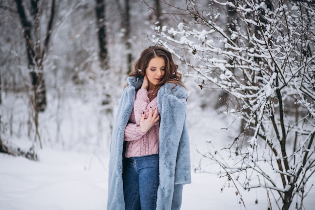 Mujer joven caminando en un parque de invierno
