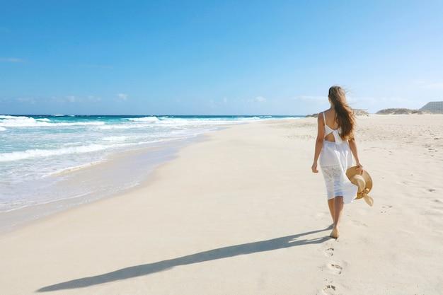 Mujer joven caminando por la playa salvaje vacía en corralejo, islas canarias
