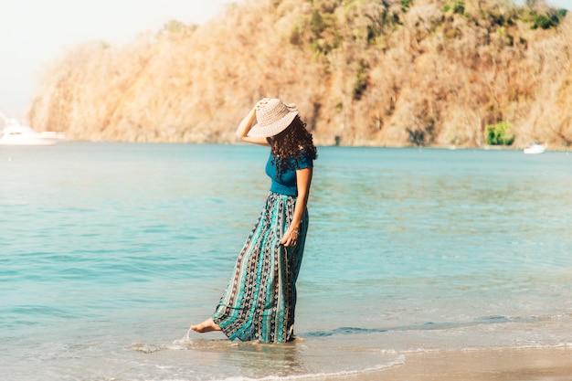 Mujer joven caminando por la playa vacía