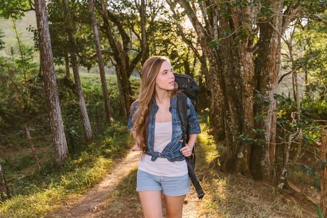 Mujer joven caminando por la pista de tierra en el bosque