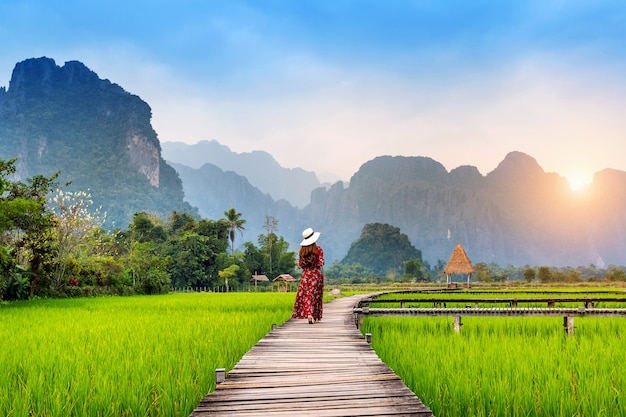 Mujer joven caminando por el sendero de madera con campo de arroz verde en vang vieng, laos.