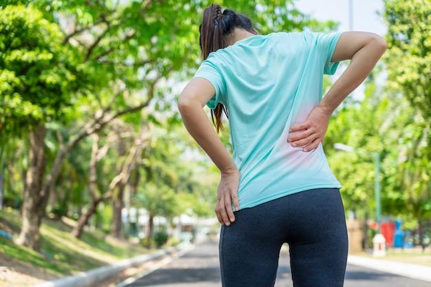 Mujer joven en el camino corriente en el parque que tiene un dolor de espalda.