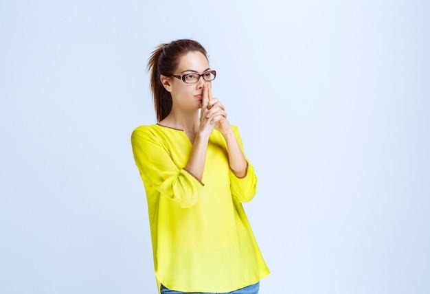 Mujer joven en camisa amarilla mostrando signo de pistola en la mano