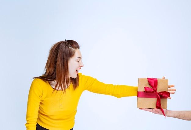 Mujer joven con camisa amarilla se ofrece una caja de regalo de cartón con cinta roja y mano anhelante para tomarla