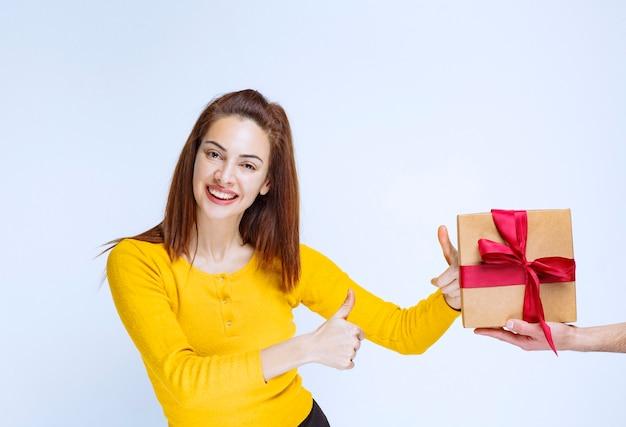 A una mujer joven con camisa amarilla se le ofrece una caja de regalo de cartón con cinta roja y muestra un signo de mano positivo