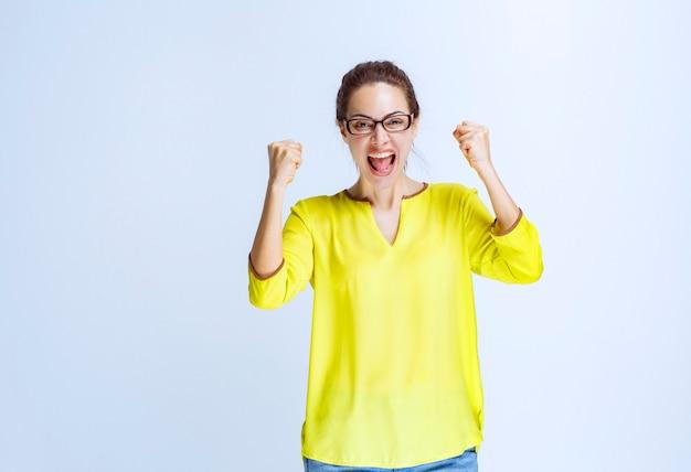 Mujer joven con camisa amarilla sintiéndose poderosa y motivada