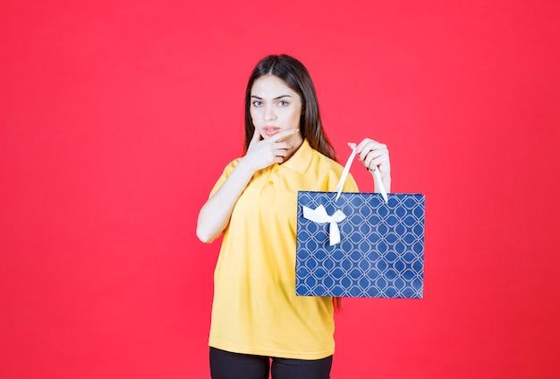 Mujer joven con camisa amarilla sosteniendo una bolsa de compras azul y parece confundida y pensativa