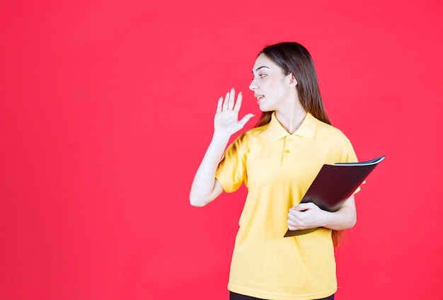 Mujer joven con camisa amarilla sosteniendo una carpeta negra, apuntando y llamando a su colega