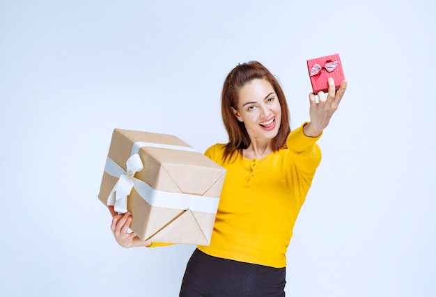 Mujer joven en camisa amarilla sosteniendo un rojo y cajas de regalo de cartón