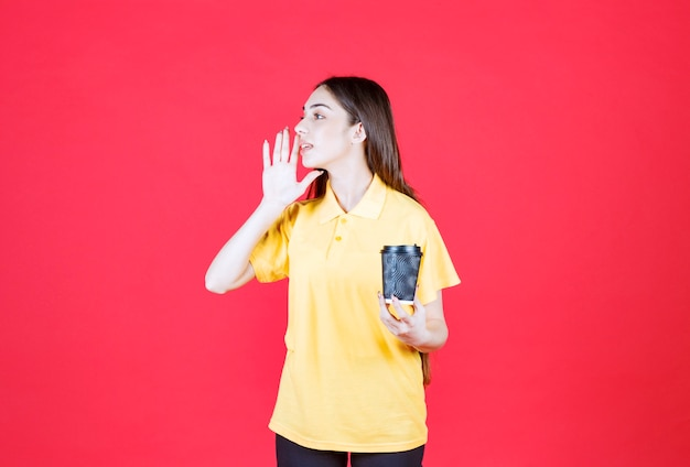 Mujer joven en camisa amarilla sosteniendo una taza de café desechable negra y llamando a alguien