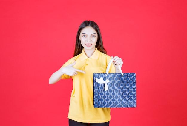 Mujer joven, en, camisa amarilla, tenencia, un, azul, bolsa de compras