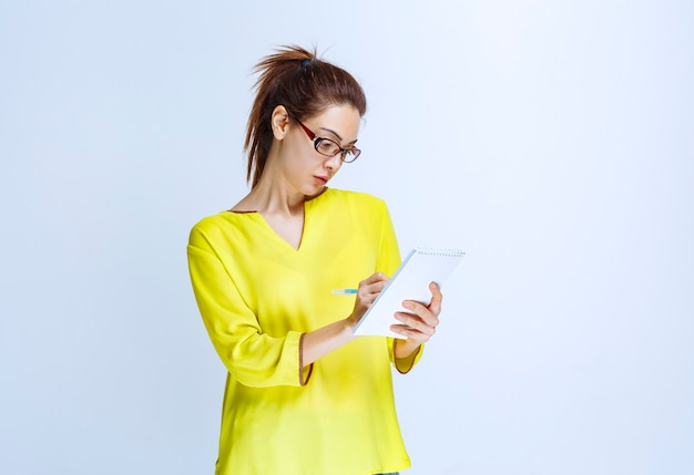 Mujer joven con camisa amarilla tomando sus notas mientras el profesor está hablando