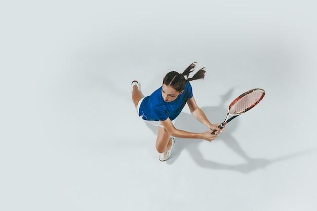 Mujer joven con camisa azul jugando al tenis. golpea la pelota con una raqueta. vista superior.