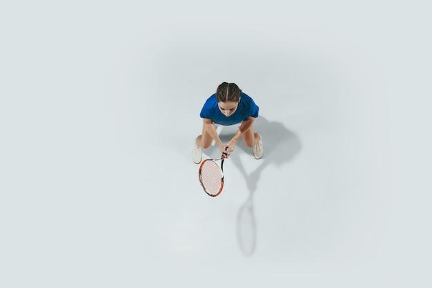 Mujer joven con camisa azul jugando al tenis. golpea la pelota con una raqueta.