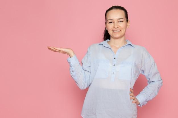Mujer joven en camisa azul sonriendo en la pared rosa