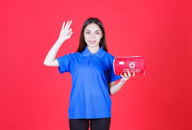 Mujer joven con camisa azul sosteniendo un botiquín de primeros auxilios rojo y mostrando un signo de mano positivo