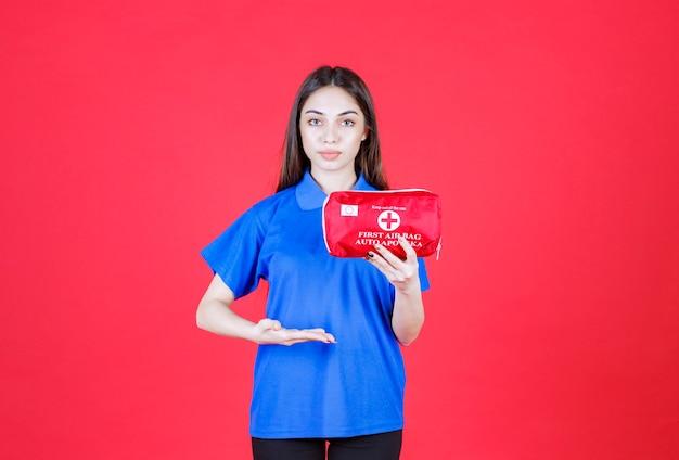 Mujer joven con camisa azul sosteniendo un botiquín de primeros auxilios rojo