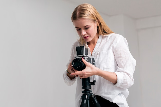 Mujer joven en camisa blanca ajustando la lente de la cámara