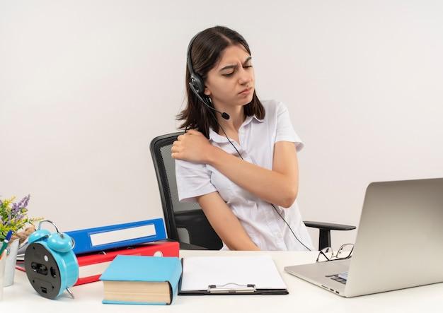 Mujer joven con camisa blanca y auriculares con un micrófono con aspecto de malestar tocando su hombro sintiendo dolor sentado en la mesa con carpetas y portátil sobre pared blanca