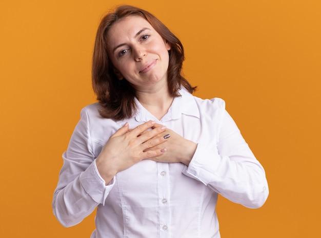 Mujer joven con camisa blanca mirando al frente con una sonrisa en la cara cogidos de la mano en el pecho sintiéndose agradecido de pie sobre la pared naranja