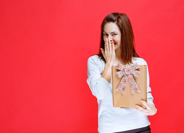 Mujer joven con camisa blanca sosteniendo una caja de regalo de cartón, cubriendo la boca y sonriendo