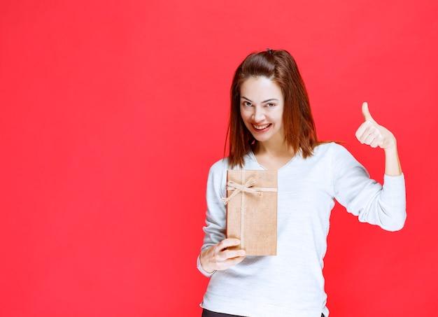 Mujer joven con camisa blanca sosteniendo una caja de regalo de cartón y mostrando un signo de mano positivo