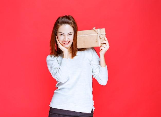 Mujer joven con camisa blanca sosteniendo una caja de regalo de cartón y parece sorprendida