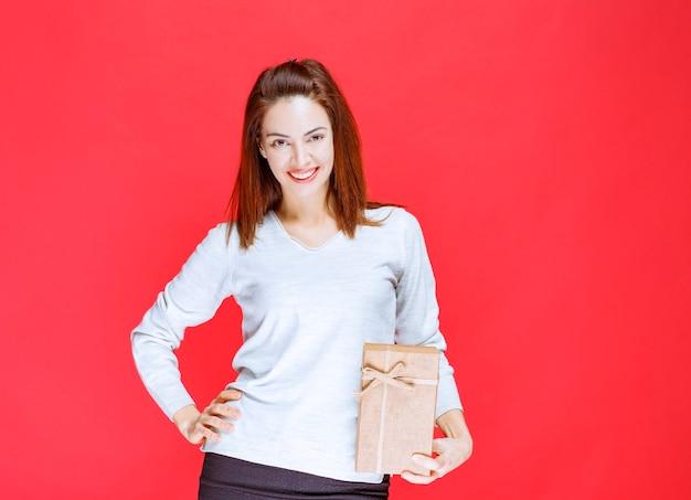 Mujer joven con camisa blanca sosteniendo una caja de regalo de cartón