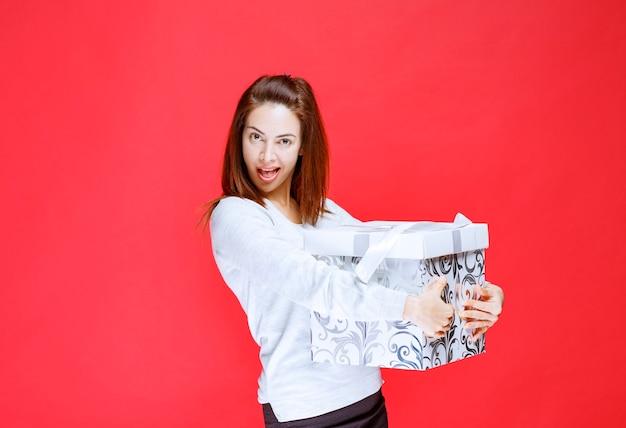 Mujer joven con camisa blanca sosteniendo una caja de regalo impresa