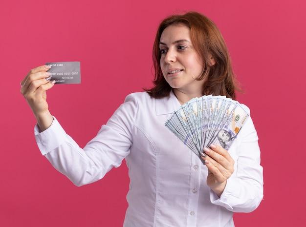 Mujer joven con camisa blanca sosteniendo dinero en efectivo mirando la tarjeta de crédito en su mano feliz y positiva sonriendo de pie sobre la pared rosa