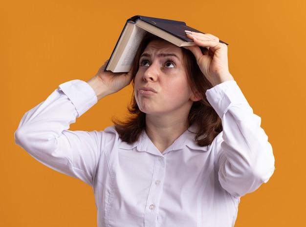 Mujer joven con camisa blanca sosteniendo un libro abierto sobre su cabeza mirando hacia arriba confundido de pie sobre la pared naranja