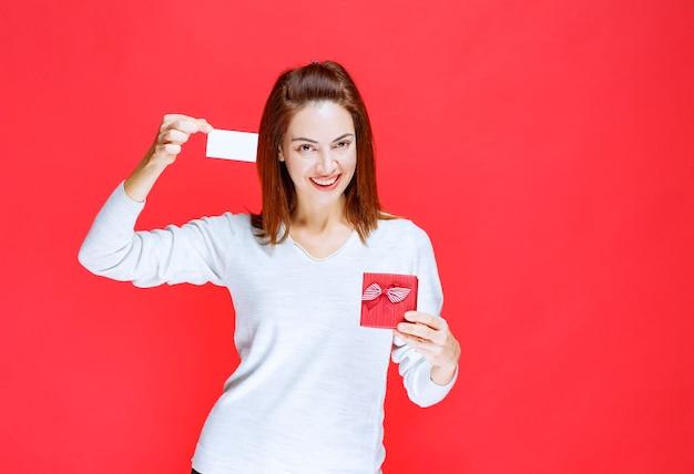 Mujer joven con camisa blanca sosteniendo una pequeña caja de regalo roja y presentando su tarjeta de visita