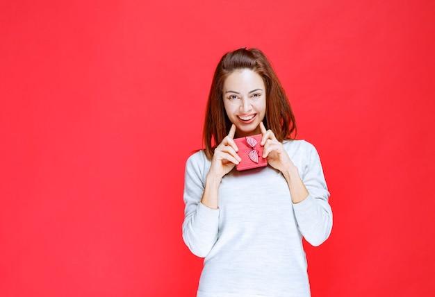 Mujer joven con camisa blanca sosteniendo una pequeña caja de regalo roja
