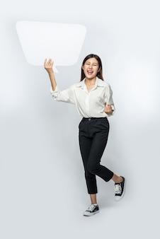 Una mujer joven con una camisa blanca sosteniendo un símbolo de cuadro de pensamiento