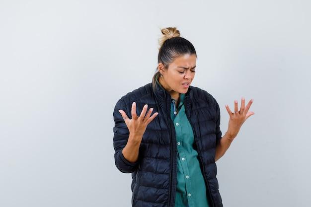 Mujer joven en camisa, chaqueta acolchada levantando las manos, mirando hacia abajo y mirando nostálgico, vista frontal.
