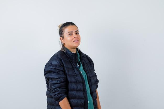 Mujer joven en camisa, chaqueta acolchada y mirando confiada. vista frontal.