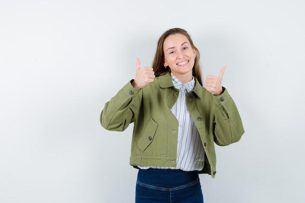 Mujer joven en camisa, chaqueta mostrando doble pulgar hacia arriba y mirando feliz, vista frontal.
