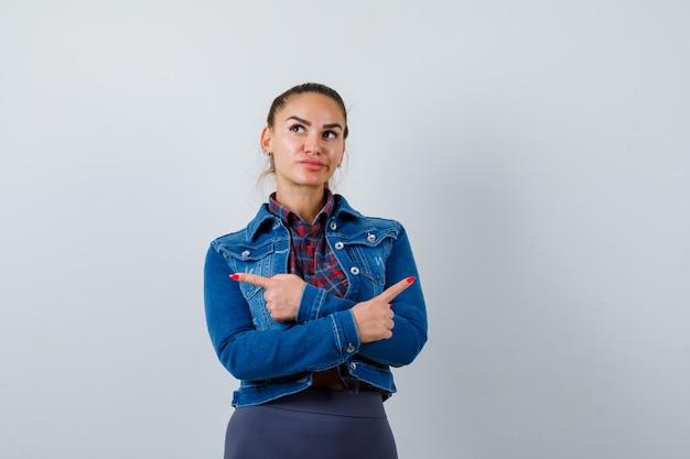 Mujer joven en camisa a cuadros, chaqueta de jean apuntando a un lado con los brazos cruzados y mirando pensativo, vista frontal.