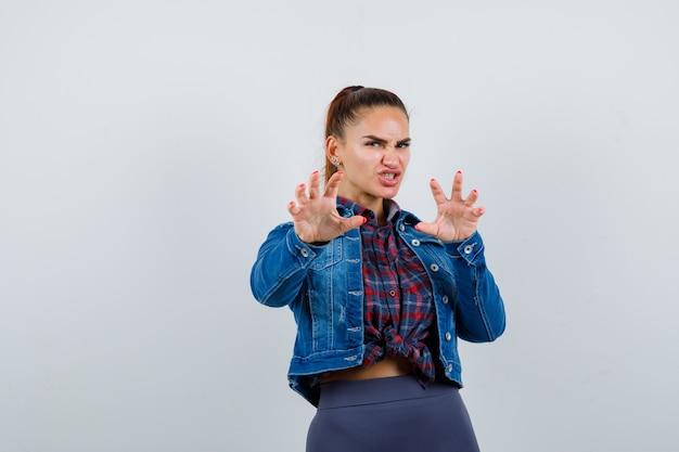 Mujer joven en camisa a cuadros, chaqueta de jean haciendo gesto de garra como gato y mirando agresivo, vista frontal.