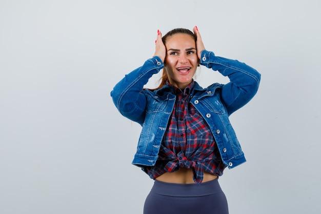 Mujer joven en camisa a cuadros, chaqueta, pantalón con las manos en la cabeza y mirando alegre, vista frontal.