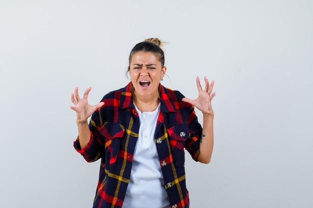 Mujer joven en camisa a cuadros gritando con las manos cerca de la cabeza y mirando agresivo, vista frontal.