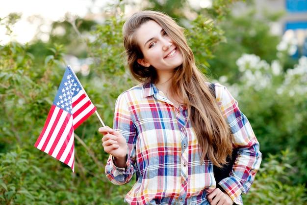 Mujer joven en camisa a cuadros y pantalones cortos con bandera americana